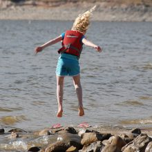 child jumping near water