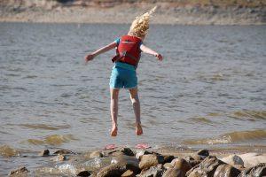 child jumping near water