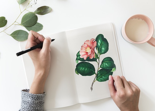 a hand holding a pen, poised over a journal with a blank page on one side and a drawing of a pink flower on the other