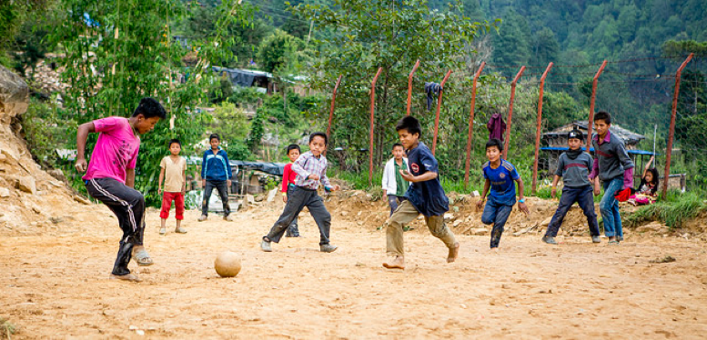 Boys playing soccer on the ground that was newly leveled to rebuild their school.