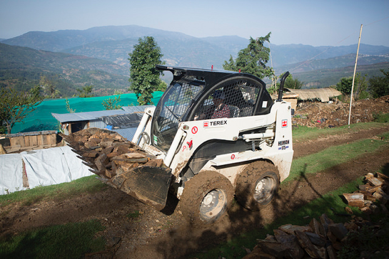 Jacob driving the Bobcat to clear earthquake rubble, so new homes can be built.