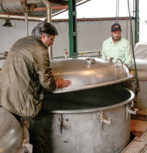 Two men lowering the large metal lid of a distilling chamber.