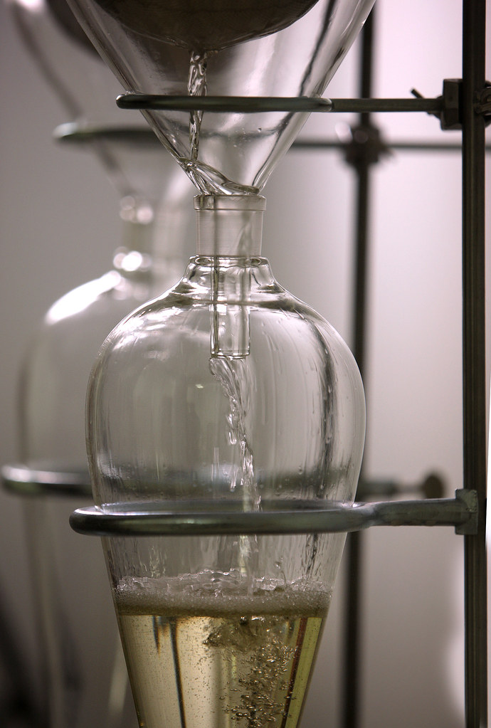 a pure therapeutic grade essential oil being distilled into a clear glass vial