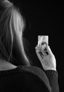 girl staring into a small handheld mirror